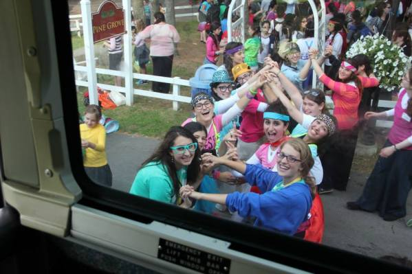 "counselors form a ""tunnel of love"" greeting new campers as they come off the bus to camp"